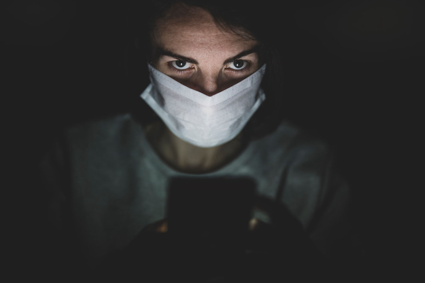 person wearing mask in the dark looking at phone