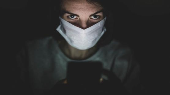 person wearing face mask looking at phone