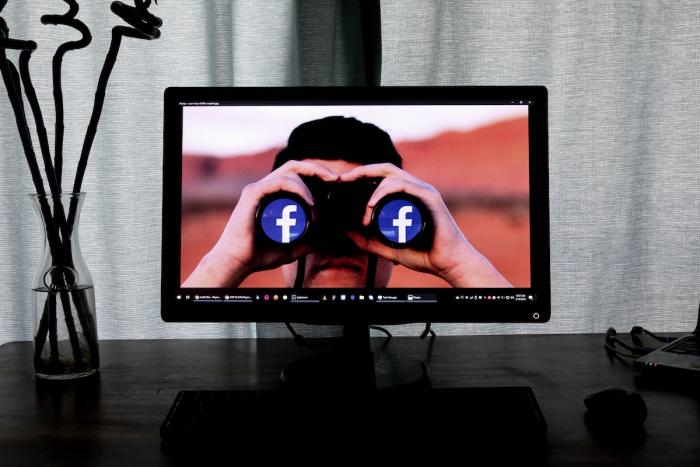 screen with individual holding binoculars with facebook sign on end