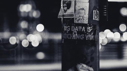 Image of signpost with poster 'big data is watching you'