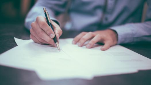 Man writting on paper on a desk