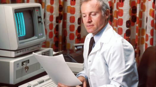 Old school male doctor on computer