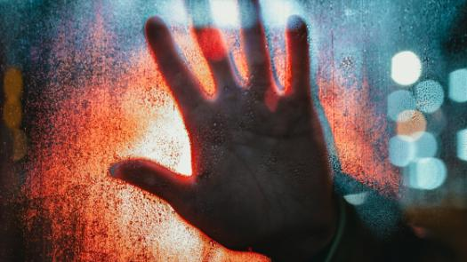 Hand on window in red and blue