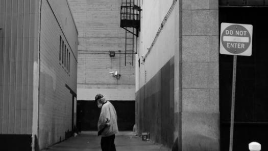 Man walking past alley in black and white