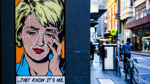 "Street art portrait on a wall with a caption ""they know it's me"""