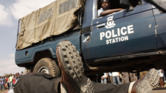 kenyan police car next to a corps