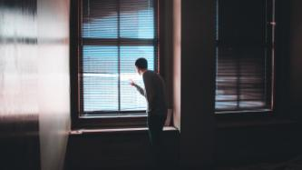 Man looking at the window behind curtains