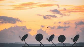 Satellite dishes against sunset background