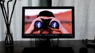 PC monitor showing individual with binoculars with Facebook image